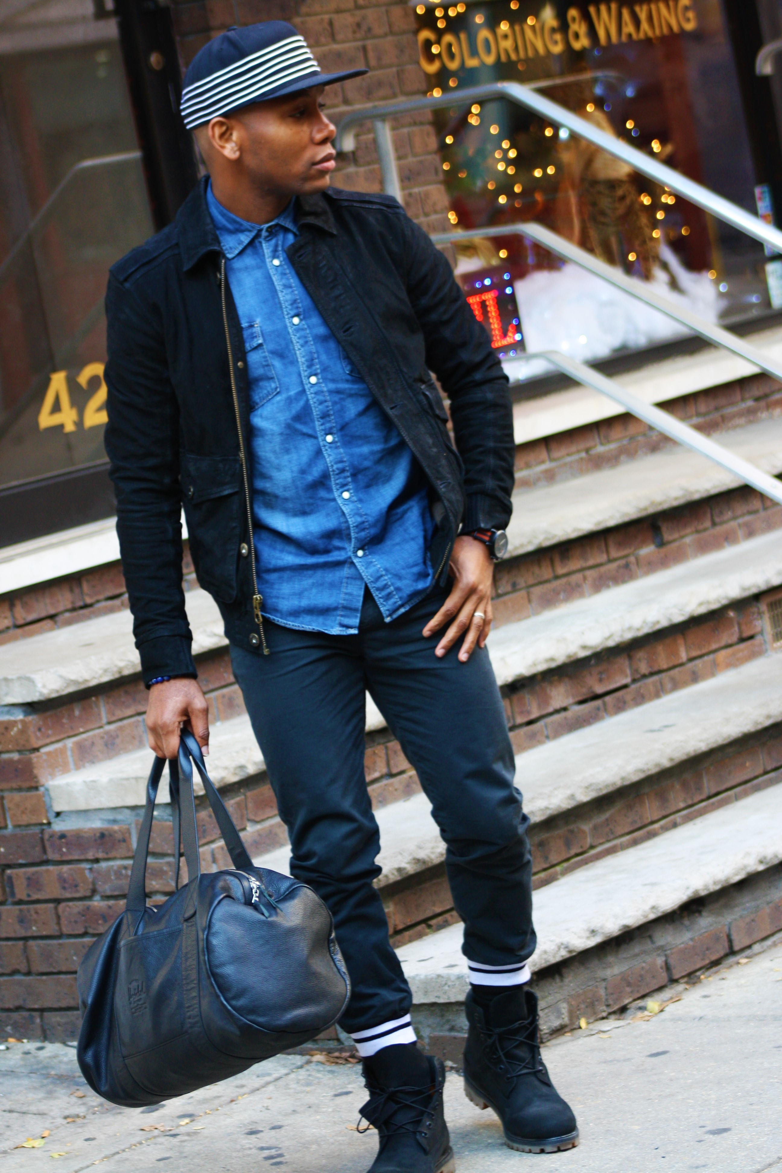 Sabir M. Peele of Men's Style Pro wearing Timberland Tenon Jacket & Black Boots with Grungy Gentleman Varsity Joggers w/ Mitchell & Ness Collaboration Hat